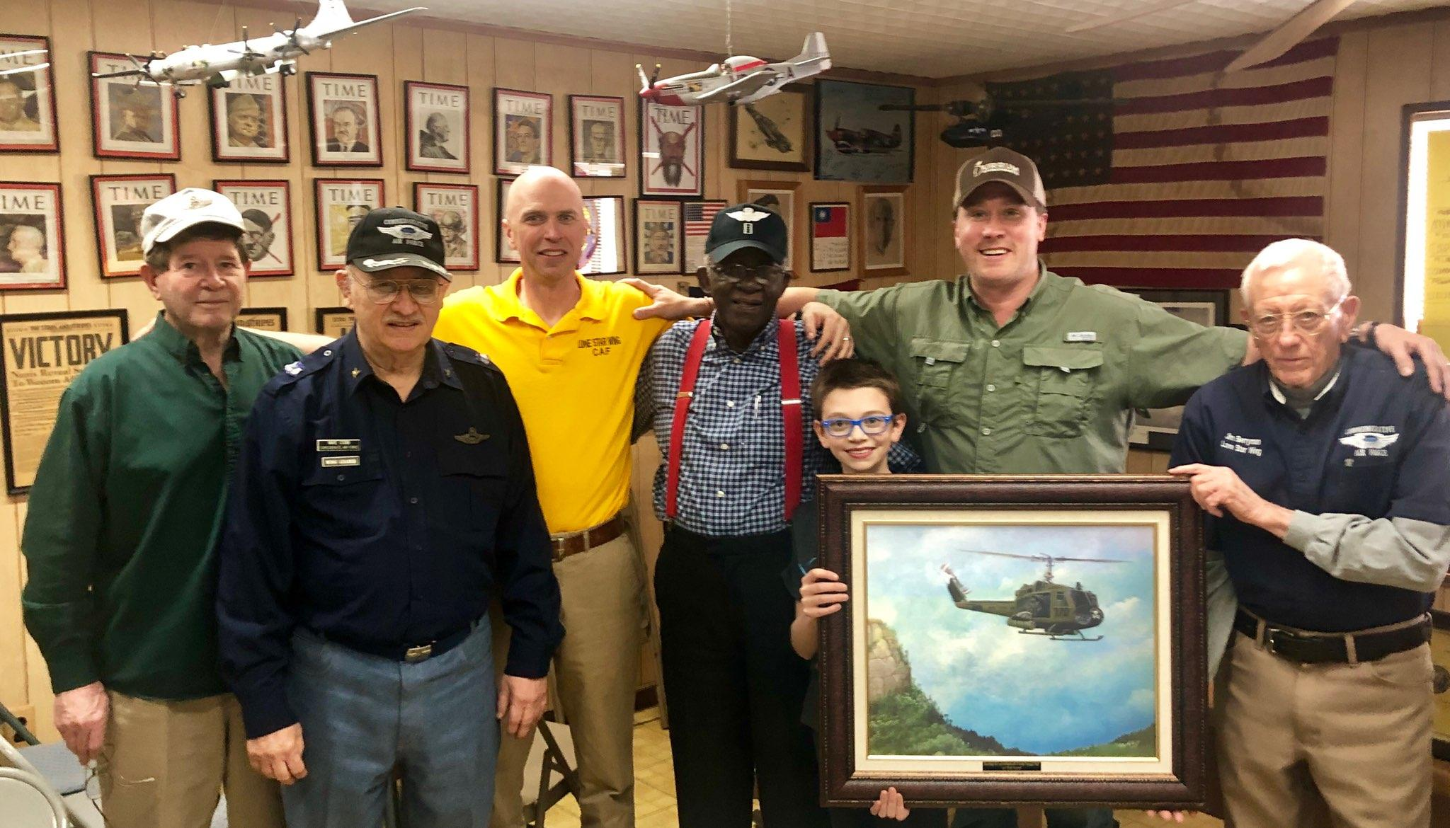 Photo of some of the members of the Lone Star Wing of the Commemorative Air Force.  Left to Right: Doyle Curry, Mike Cobb, Jimmy Page, Bob Snead, Wilson Page, Travis Keeney, and Jim Berryman.  Pictured with an original artwork donated by Bob of his UH-1C gunship 136, entitled
